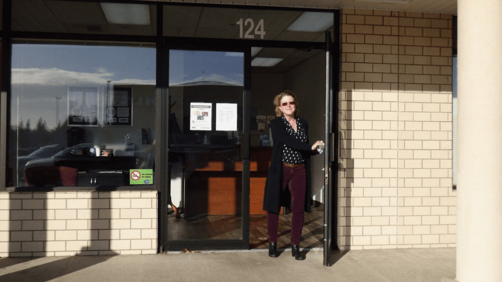 Julie standing outside South Sound Audiology clinic